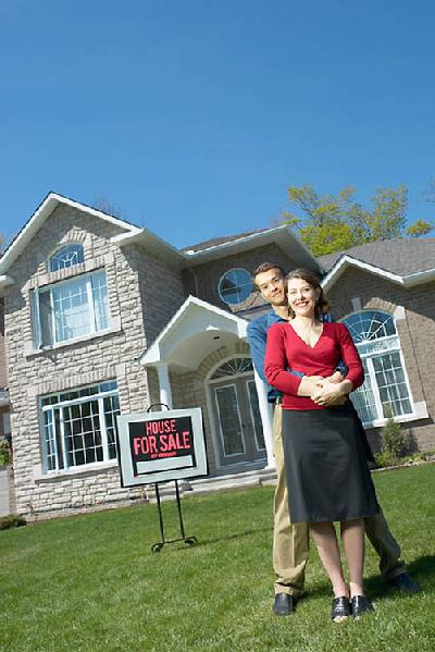 A happy couple standing in the front yard of a house with a for sale sign